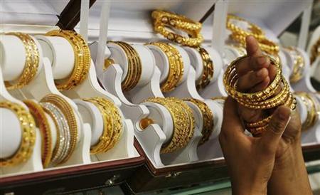 A customer tries gold bangles inside a jewellery showroom at Noida in Uttar Pradesh April 21, 2011. REUTERS/Parivartan Sharma/Files