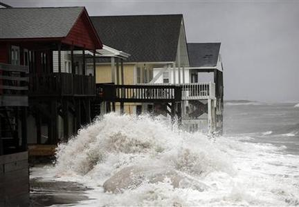 A wave crashes over the protecting sandbags in front of the houses on the east side of Ocean Isle Beach during Hurricane Sandy in Ocean Isle Beach, North Carolina, October 27, 2012. REUTERS-Randall Hill