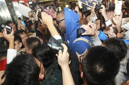 Fans take photos of former NBA player Tracy McGrady as he arrives at Qingdao airport, Shandong province October 24, 2012. REUTERS/China Daily