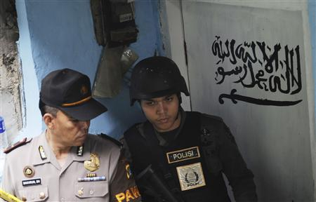 An official from the Special Detachment 88 squad and a police officer stand guard outside the house of a suspected militant after a raid in Jakarta October 27, 2012. REUTERS/Jefri Tarigan