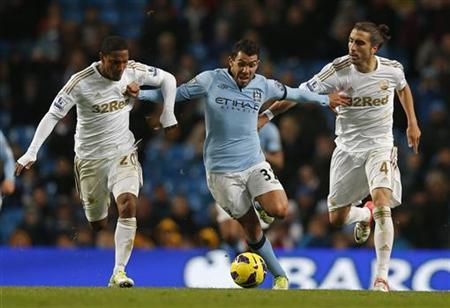 Manchester City's Carlos Tevez (C) is challenged by Swansea City's Jonathan de Guzman (L) and Chico Flores (R) during their English Premier League soccer match at The Etihad Stadium in Manchester, northern England, October 27, 2012. REUTERS/Phil Noble
