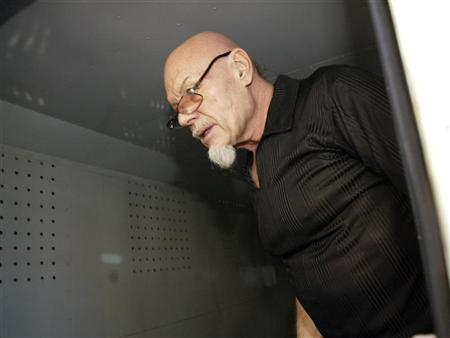 British 'glam rocker' Gary Glitter stands inside a police truck before being taken to prison after the verdict in Vung Tau, a resort town 120 km (75 miles) southeast of Ho Chi Minh City in this March 3, 2006 file photo. REUTERS/Zainal Abd Halim/Files