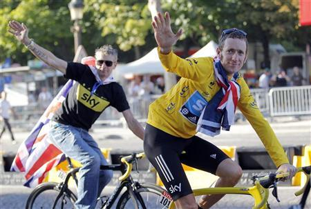 Sky Procycling rider and leader's yellow jersey Bradley Wiggins of Britain and Sky Procycling Sport director Sean Yates (L) celebrate with British national flags on the Champs Elysees after the final stage of the 99th Tour de France cycling race in Paris, July 22, 2012. REUTERS/Stephane Mahe