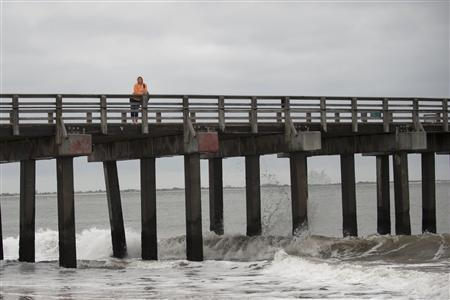A woman looks out from the boardwalk in Coney Island as waves come ashore in New York, October 28, 2012. REUTERS/Keith Bedford