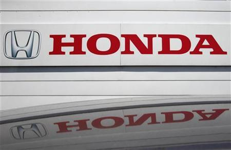 A logo of Honda Motor Co is reflected on a roof of a vehicle at a Honda dealer in Kawasaki, south of Tokyo July 31, 2012. REUTERS/Yuriko Nakao