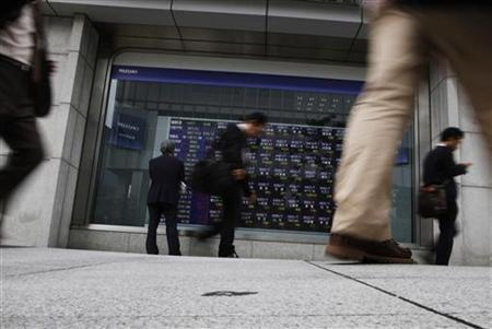 Businessmen walk past an electronic board displaying market indices outside a brokerage in Tokyo October 17, 2012. REUTERS/Issei Kato/Files