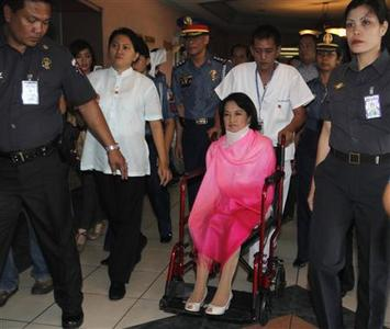 Former Philippine President Gloria Macapagal Arroyo, now a sitting lawmaker in the lower house of Congress, sits on a wheelchair as she makes her way towards the Sandiganbayan anti-graft court in Quezon City, Metro Manila October 29, 2012. The Philippine court entered a ''not guilty'' plea for Arroyo on Monday during her trial for plunder charges of misusing state lottery fund, a litmus test for the government's ability to tackle entrenched corruption in the poor Southeast Asian nation. REUTERS/Cheryl Ravelo