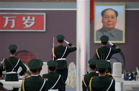 Paramilitary police officers salute in front of a giant portrait of the late chairman Mao Zedong during a flag-lowering ceremony on Beijing's Tiananmen Square, October 24, 2012. REUTERS/Jason Lee