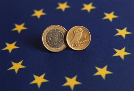 An one Euro (L) and one Greek Drachma coins are displayed on an European flag in this picture illustration taken in Istanbul June 14, 2012. REUTERS/Murad Sezer