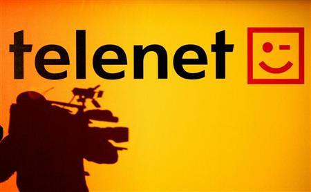 The shadow of a cameraman is seen beside the Belgian cable operator Telenet logo during a news conference in Brussels September 22, 2005. REUTERS/Thierry Roge