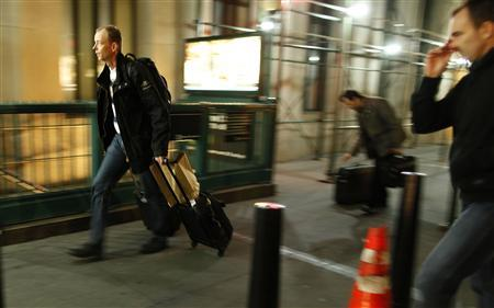 People make their way, with luggage, to the Wall Street station, to get out of lower Manhattan, in New York October 28, 2012. REUTERS/Carlo Allegri