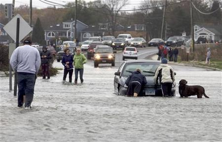 Pedestrians come to the aid of a motorist stuck on a flooded-out road along the shoreline area of Milford, Connecticut ahead of Hurricane Sandy October 29, 2012. REUTERS/Michelle McLoughlin