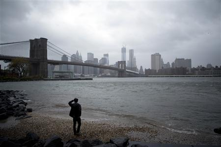 A man watches rising waters on the East River from Brooklyn as Hurricane Sandy made its approach in New York October 29, 2012. REUTERS/Andrew Kelly