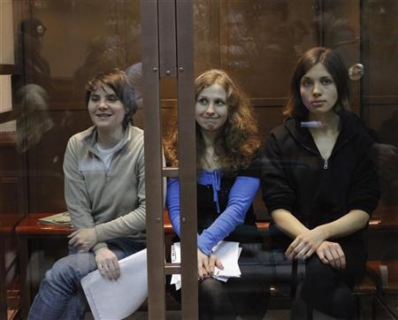 Members of the female punk band ''Pussy Riot'' (L-R) Yekaterina Samutsevich, Maria Alyokhina and Nadezhda Tolokonnikova sit in a glass-walled cage before a court hearing in Moscow October 10, 2012. REUTERS/Maxim Shemetov