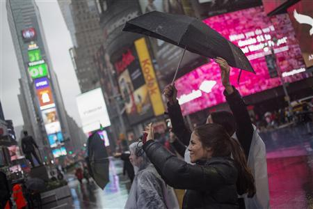 Visitors hold umbrellas while taking photos during rainfall at Times Square in New York October 29, 2012. REUTERS/Adrees Latif