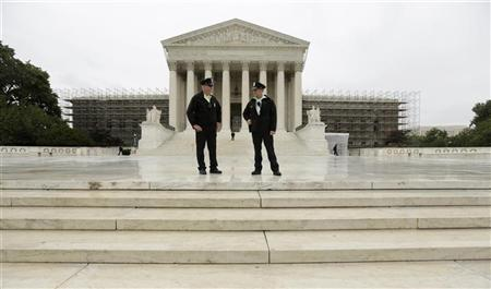 Policemen talk in front of the U.S. Supreme Court in Washington June 18, 2012. REUTERS/Kevin Lamarque