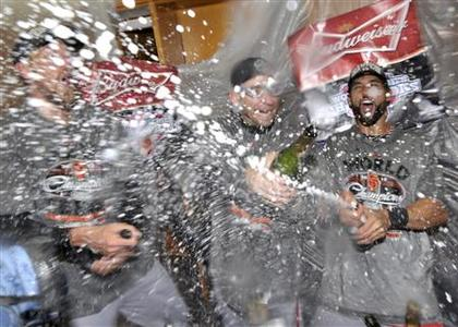 San Francisco Giants' Angel Pagan (R) and Marco Scutaro spray champagne as they celebrate defeating the Detroit Tigers in Game 4 to win the MLB World Series baseball championship in Detroit, Michigan, October 28, 2012. REUTERS/Mike Cassese