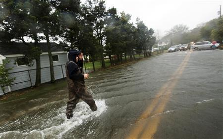 A man walks through a street flooded by the storm surge from Hurricane Sandy in Shinnecock Hills, New York, October 29, 2012. REUTERS/Lucas Jackson