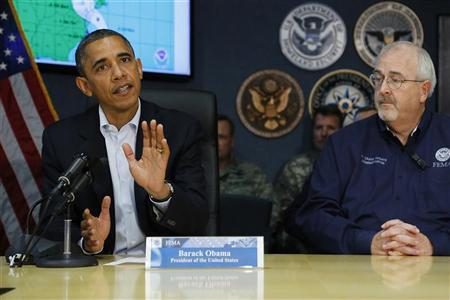 U.S. President Barack Obama, seated with Federal Emergency Management Agency (FEMA) Administrator William Craig Fugate (R), urges Americans to take safety measures after a briefing about Hurricane Sandy, as it threatens the East Coast, at FEMA headquarters in Washington, October 28, 2012. REUTERS/Jonathan Ernst