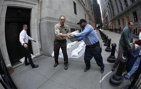 New York Stock Exchange workers place sand bags in front of doors and over electrical vaults at the exchange in New York October 28, 2012. REUTERS/Carlo Allegri