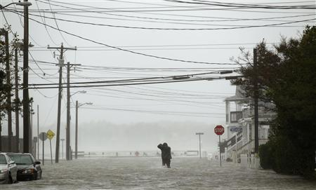 Powerlines hang overhead as a man wades through a street flooded during Hurricane Sandy in Ocean City, Maryland October 29, 2012. REUTERS/Kevin Lamarque