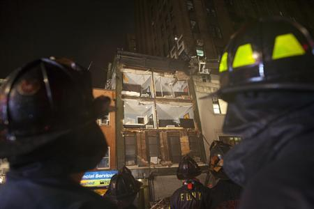 Fire fighters look at a partially collapsed four-storey apartment building in Manhattan as Hurricane Sandy made its approach to New York October 29, 2012. REUTERS/Andrew Kelly