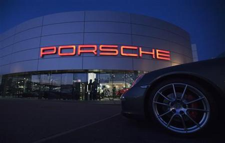An illuminated Porsche logo is pictured on a building of a Porsche retail centre in Niederwangen, outside Bern March 9, 2012. REUTERS/Michael Buholzer