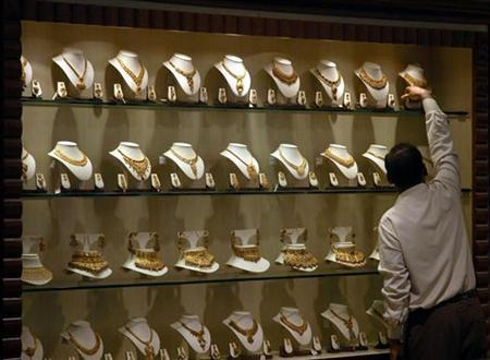 A salesman arranges gold necklaces at a jewellery showroom in Chennai April 27, 2009. REUTERS/Babu/Files