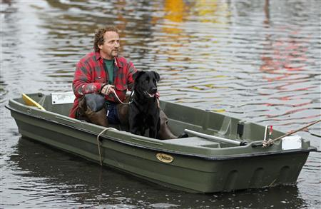 Ray Cilli and his dog Woubie are rescued from flood waters brought on by Hurricane Sandy in Little Ferry, New Jersey, October 30, 2012. Millions of people across the eastern United States awoke on Tuesday to scenes of destruction wrought by monster storm Sandy, which knocked out power to huge swathes of the nation's most densely populated region, swamped New York's subway system and submerged streets in Manhattan's financial district. REUTERS/Adam Hunger