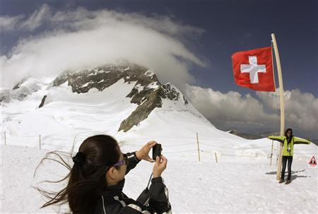 Tourists take pictures on the Plateau (altidude 3475 metres/11401 feet) at the Jungfraujoch July 25, 2012. REUTERS/Arnd Wiegmann
