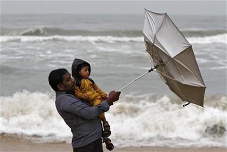 A man carrying his child tries to hold an umbrella at Marina beach in Chennai October 30, 2012. REUTERS/Babu