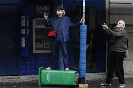Retired persons take pictures during a nationwide demonstration to defend their pensions and purchasing power in Paris, October 11, 2012. REUTERS/Gonzalo Fuentes