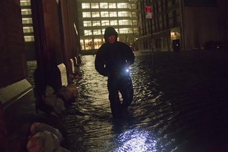 A security guard walks through a flooded street in the financial district of Manhattan, New York October 30, 2012. NYSE Euronext said it is preparing to implement a new contingency plan to help resume stalled U.S. equity trading, and added that its famed trading floor is not yet damaged by Hurricane Sandy. REUTERS/Adrees Latif