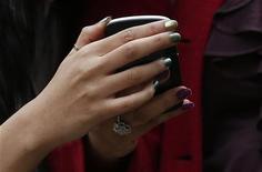Duas mulheres olham aparelho celular na Oxford Street, em Londres. A operadora de telefonia móvel EE lançou sua rede 4G em 11 cidades britânicas nesta terça-feira, o que lhe oferece vantagem diante dos rivais na corrida para conduzir os consumidores britânicos à era da banda larga de alta velocidade, que permite chats em vídeo e navegação rápida na Internet móvel. 29/10/2012 REUTERS/Suzanne Plunkett