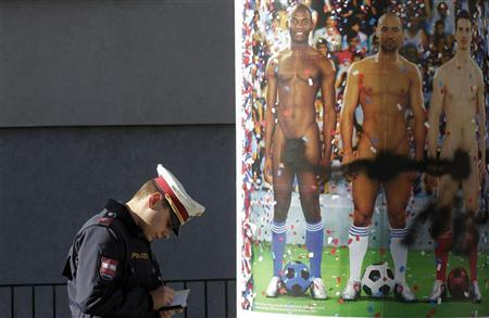 A police officer stands next to a poster with naked soccer players daubed with spray paint, advertising an art exhibition in Vienna October 17, 2012. REUTERS/Herwig Prammer