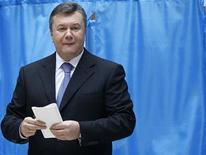 Ukrainian President Viktor Yanukovich holds his ballot as he visits a polling station during the parliamentary elections in Kiev, October 28, 2012. REUTERS/Gleb Garanich