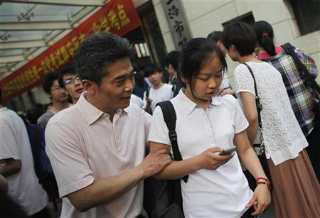 A student and her father leave Shanghai No.1 High School after finishing China's annual national college entrance exam in Shanghai June 8, 2012. About 9.15 million people will take the exam to vie for 6.85 million vacancies in the country's universities and colleges, said China's education ministry, according to Xinhua News Agency. REUTERS/Carlos Barria