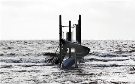 A playground apparatus stands surrounded by water pushed up by Hurricane Sandy in Bellport, New York, October 30, 2012. REUTERS-Lucas Jackson