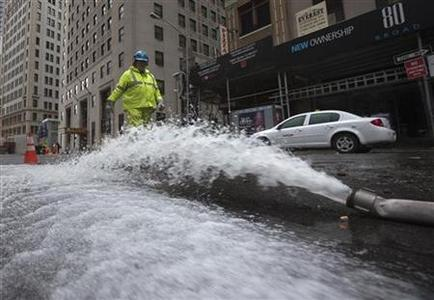 A worker walks past a hose pumping water out of underground parking structures in the financial district of Lower Manhattan, New York October 30, 2012. REUTERS/Adrees Latif