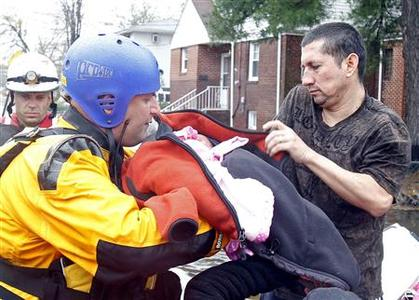A resident passes his baby to an emergency personnel as they are rescued from flood waters brought on by Hurricane Sandy in Little Ferry, New Jersey, October 30, 2012. Millions of people across the eastern United States awoke on Tuesday to scenes of destruction wrought by monster storm Sandy, which knocked out power to huge swathes of the nation's most densely populated region, swamped New York's subway system and submerged streets in Manhattan's financial district. REUTERS/Adam Hunger