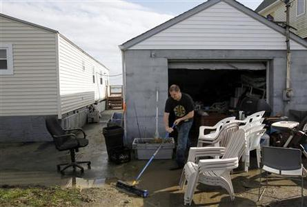 Mike Starkie sweeps mud out of his garage as he cleans up from Hurricane Sandy in Fairhaven, Massachusetts October 30, 2012. REUTERS/Jessica Rinaldi