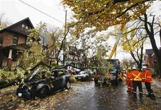 Power workers look at a car that was burned out in an electrical fire after a tree fell over a power line due to the remnants of Hurricane Sandy in Toronto, October 30, 2012. REUTERS/Mark Blinch