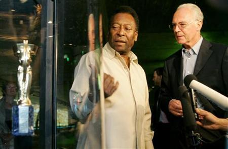 Soccer legend Pele of Brazil and former German player Franz Beckenbauer (R) stand beside a replica of the first World Cup trophy 'Coupe Jule Rimet' during their visit to the exhibition 'Pelestation' in Berlin June 29, 2006. REUTERS/Arnd Wiegmann/Files