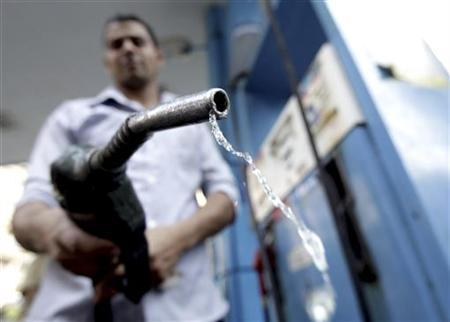 A worker holds up a fuel pump nozzle after filling up the tank of a car at a petrol station in Cairo October 3, 2012. REUTERS/Mohamed Abd El Ghany