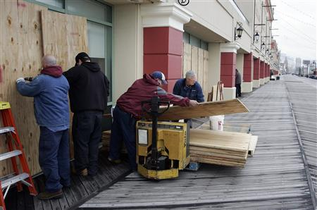 A crew from the Tropicana Casino removes plywood sheets from the windows facing the ocean on the boardwalk following the aftermath of Hurricane Sandy in Atlantic City, New Jersey, October 30, 2012. REUTERS/Tom Mihalek