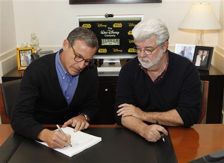 Walt Disney Company Chairman and Chief Executive Officer Bob Iger (L) and filmmaker and Chairman of the Board of Lucasfilm Ltd. George Lucas sign documents at the Walt Disney Co. in Burbank, California October 30, 2012. REUTERS/Rick Rowell/Disney/© 2012 Disney Enterprises, Inc. All rights reserved