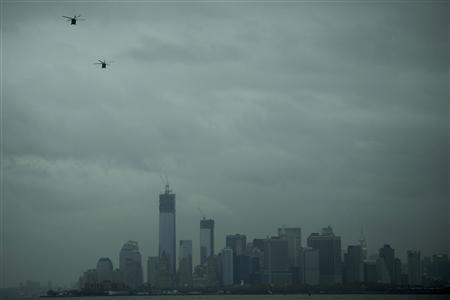 Helicopters fly over the skyline of lower Manhattan as it sits in darkness after a preventive power outage caused by Hurricane Sandy in New York October 30, 2012. REUTERS-Keith Bedford