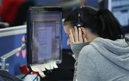 A worker on IG Index's trading floor puts her hand to her face as she speaks on the phone while markets tumble, in London, September 22, 2011. REUTERS/Andrew Winning