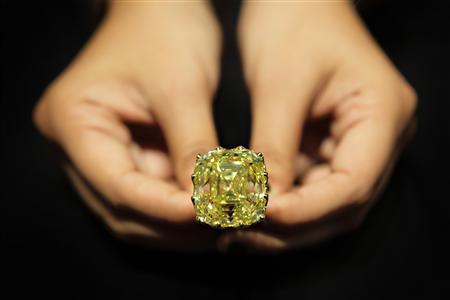 A jeweller from Vihari Jewels holds the 110-carat ''Yellow Dragon'' diamond ring during the Singapore Jewelfest 2012 exhibition in Singapore October 17, 2012. T REUTERS/Tim Chong/Files