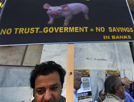 A Greek bondholder holds a sign during a protest outside the Central Bank of Greece in Athens October 31, 2012. REUTERS/Yannis Behrakis